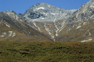 NZ grassy peak to bigger mountains in bg by Chunga-Stock