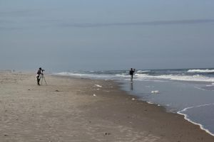 photographers on the beach by taevans