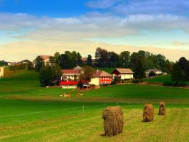 Hay bales and country village by patrickjobst