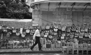 Traditional bag seller/ man passing by. by Gothumanity