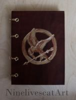 Notebook with main theme of Hunter Games by NinelivescatArt
