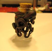 Octopus wrapped around a glass vial by clayfriends